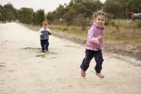 Girl running along country lane with boy behind and rural background photo