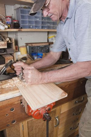 Man using routing plane on workbench with tools and odds and ends in background Stock Photo - 5551258