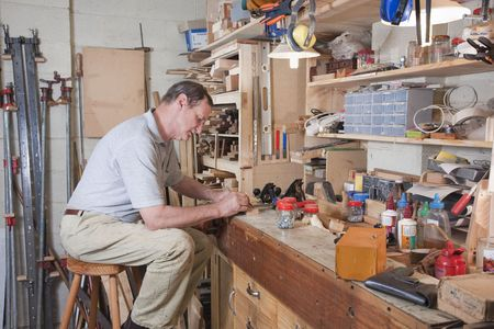 baby boomer: Man working at home workbench surrounded by equipment