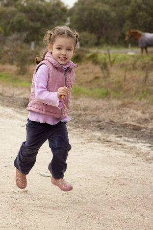 Girl running along country lane photo