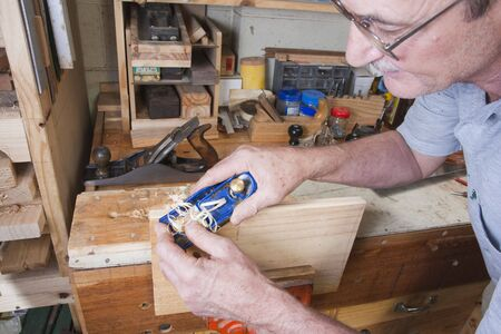 Senior man doing carpentry with edging plane on workbench Stock Photo - 5562502