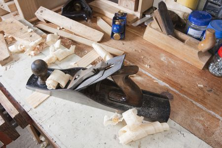 Carpentry jointing plane sitting on cluttered workbench with other tools, offcuts and wood shavings Stock Photo - 5562503