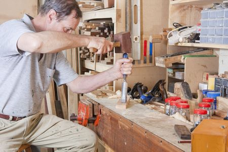 Man using chisel at workbench surrounded by tools and equipment Stock Photo - 5562505