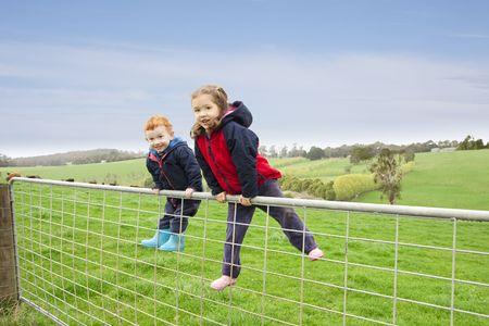 Young boy and girl on farm gate with rural farm background photo