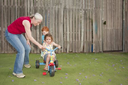 Grandmother helping two kids ride tricycle