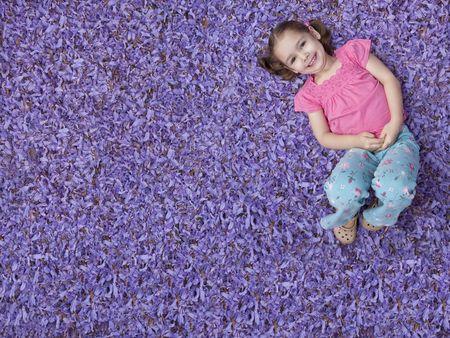 Niña acostada en la cama de flores de color púrpura Foto de archivo - 5812412