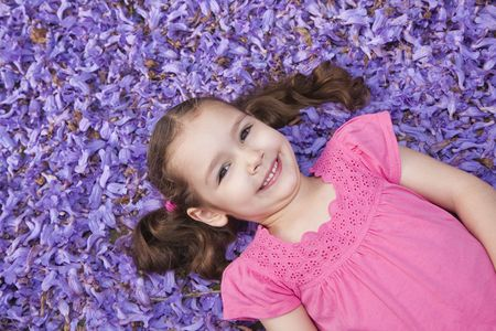 Young girl lying on ground covered with purple flowers Stock Photo - 5812414