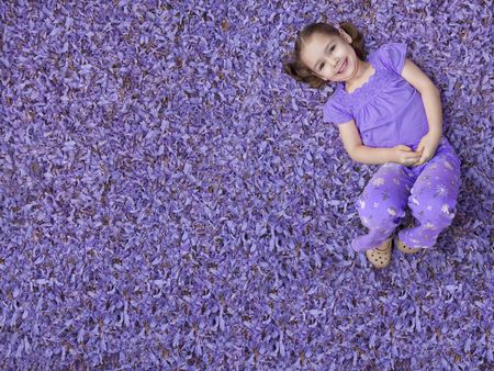 to lie: Young girl lying on purple flowers Stock Photo
