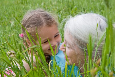 Girl laughing with her grandmother as they lie in long green grass Stock Photo