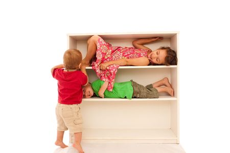 three shelves: Three young kids playing on bookshelves, two lying on the shelves, with the youngest trying to get on.