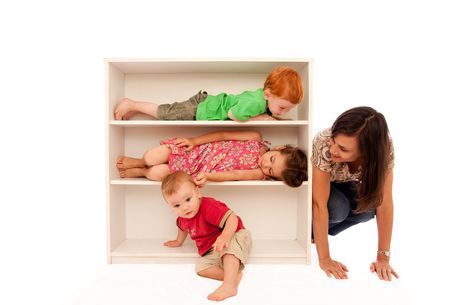 three shelves: Three kids playing hide and seek on bookshelf with mum looking