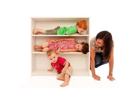 Tres niños jugando ocultar y buscan en estantería con aspecto inusual