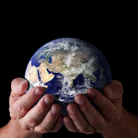 Hands holding world with isolated black background. Earth image courtesy of NASA. Concept of caring for earth