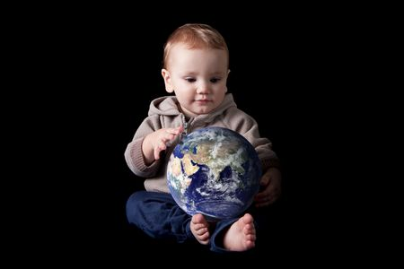 Toddler boy holding world in his lap. Isolated on black. Earth image courtesy of NASA. photo