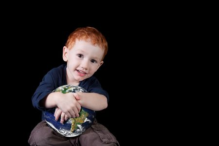 Young boy holding the world and smiling.  Stock Photo - 6726185