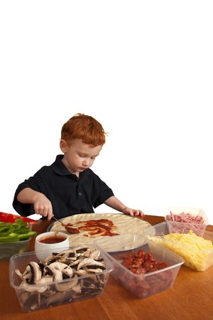 Young boy preparing homemade pizza isolated on white photo