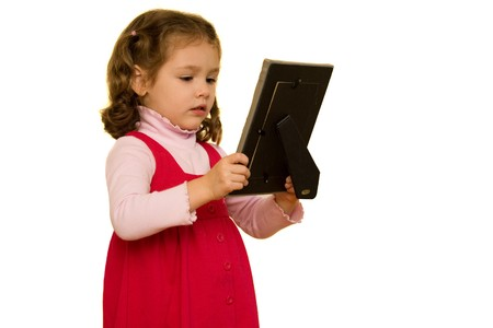reminisce: Young girl isolated on white looking at picture frame with sad facial expression