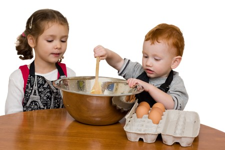 stiring: Two kids helping prepare cake in mixing bowl. Isolated on white. Stock Photo