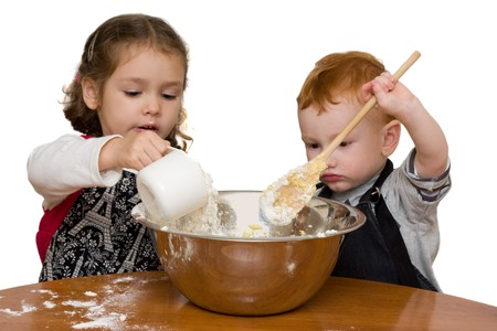 Two kids measuring and mixing into large mixing bowl. Isolated on white. photo