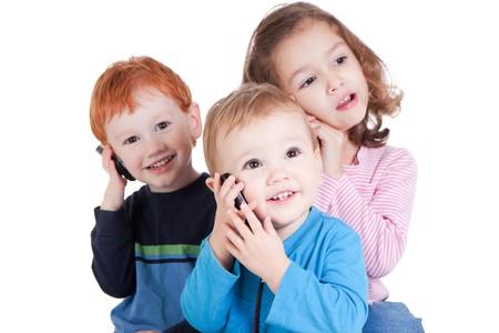mobiele telefoons: Drie gelukkige kinderen praten op mobiele telefoons. Op wit wordt geïsoleerd.