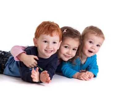 bambin: Trois enfants couch�e sur le sol ensemble. Isol�es sur blanc  Banque d'images
