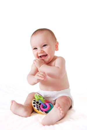 Happy baby sitting on bed and smiling, with toy. Isolated on white.