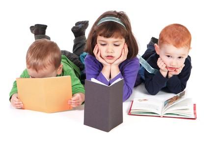 Trois enfants, lecture de livres couchée sur le plancher  Banque d'images