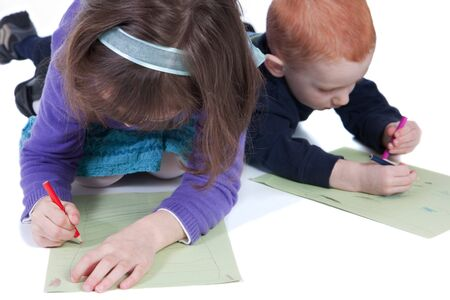 Two kids lying on floor and drawing on paper with colored pencils Stock Photo - 7369056