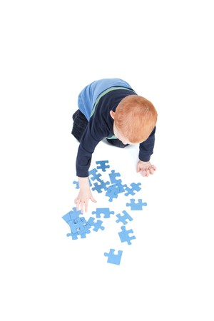 learning by doing: Young boy doing blank puzzle isolated on white