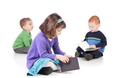 cross leg: Tres ni�os sentados en el piso y lectura de libros. Aislados en blanco con sombras.  Foto de archivo