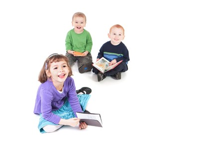 Three happy kids reading books and looking up. Isolated on white with shadows. Stock Photo