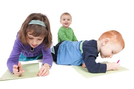 Two kids drawing on floor and a toddler watching