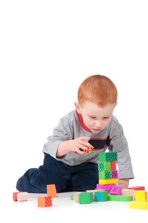 tower block: Boy building colorful block tower. Isolated on white with shadows.