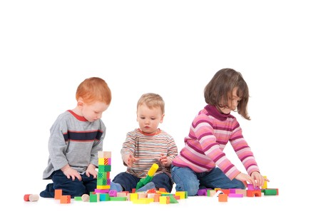 Three kids playing with wooden blocks. Isolated on white, with shadows. Standard-Bild