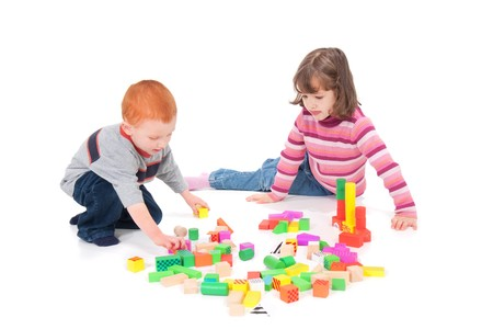 Two kids playing with colorful blocks. Isolated on white with shadows. Stock Photo