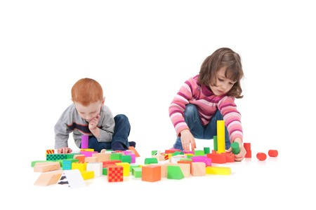 Two kids building block towers. Isolated on white with shadows Standard-Bild