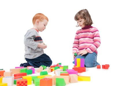 Kids playing with colorful blocks. Isolated on white with shadows