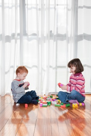Two kids playing with wooden blocks in front of window