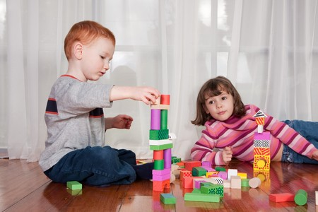Two kids playing with wooden blocks on polished floor with window behind