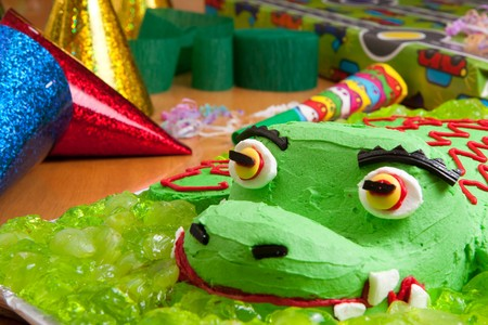 Closeup of kids birthday crocodile cake with party decorations and presents Stock Photo - 7596260