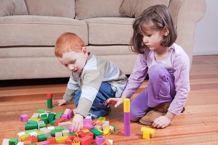 ni�as jugando: Dos ni�os jugando con bloques en frente del sof�