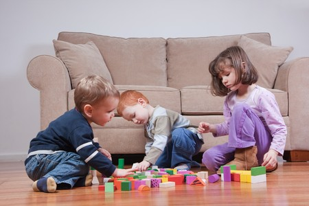 polished wood: Three preschooler kids playing with blocks