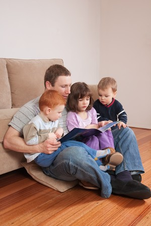 Father reading story to three kids sitting on his lap Stock Photo