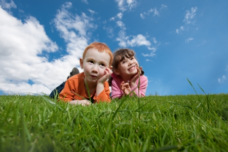 Two kids lying on top of grassy hill with blue sky background Stock Photo