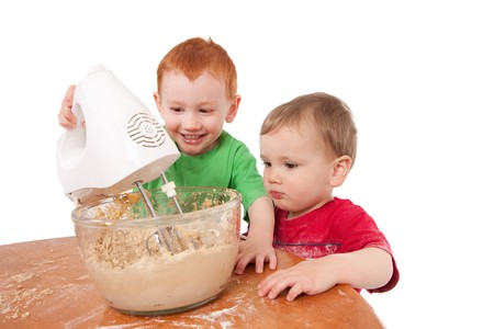 electric mixer: Boys making cake and using electric mixer. Isolated on white. Stock Photo