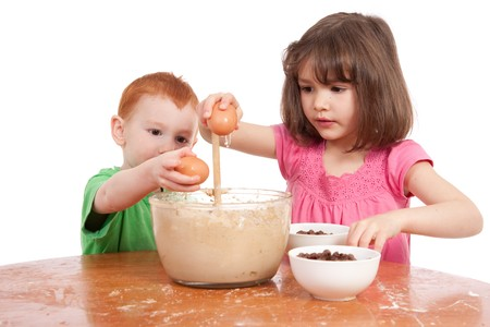messy kitchen: Kids baking chocolate chip cookies. Isolated on white. Stock Photo