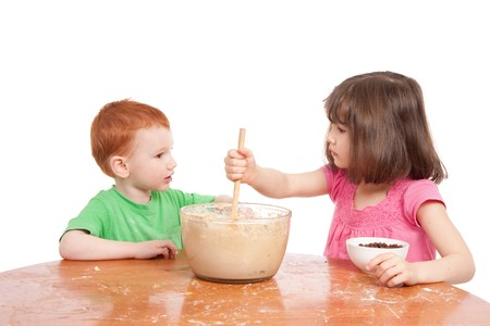 Two kids talking while baking cake. Isolated on white. photo