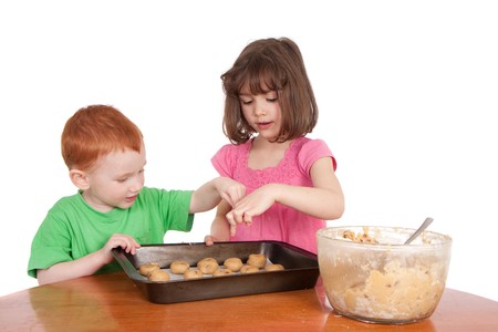 Kids counting chocolate chip cookies to bake. Isolated on white. photo