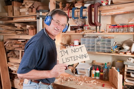 Man in workshop not listening and holding sign