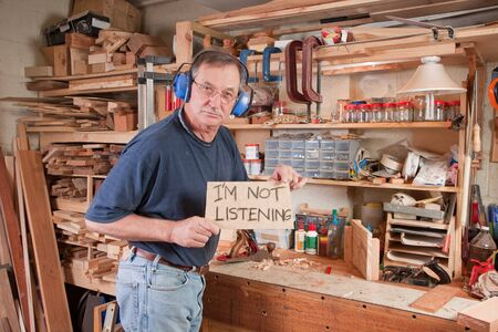 Angry senior man in workshop holding sign 'I'm not listening' to his wife Stock Photo - 8218919